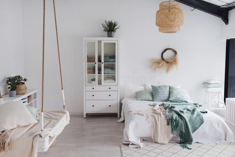 Modernt scandinavian soligt sovrum med växter och kuddar Utrymme med vita väggar och det breda fönstret eco arkivbild
