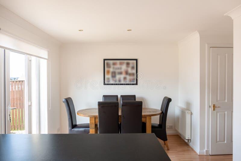 Modernt skotskt kökDinning rum med ektabellen och stolar i rena vita målade Coloirs arkivbild