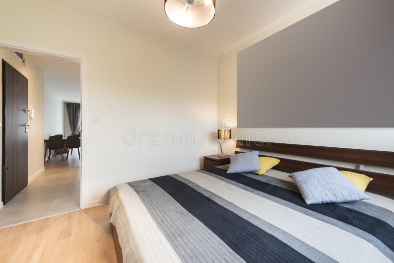 Modernt sovrum i beige avslutning royaltyfri fotografi