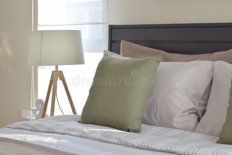 Modernt sovrum med den gröna kudden och den dekorativa trälampan arkivbild