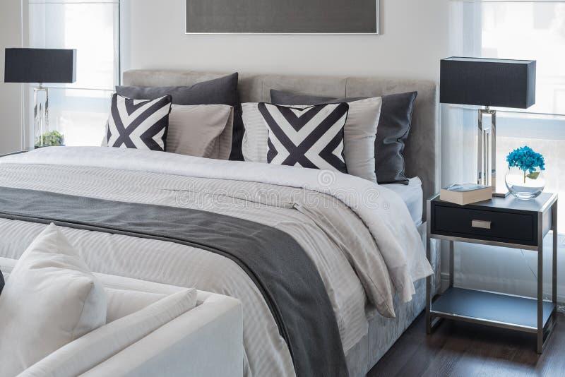Modernt sovrum med den vita säng- och svartlampan royaltyfria foton
