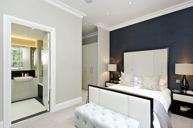 Modernt sovrum med konungformatsäng med lyxig märkes- päls royaltyfri bild