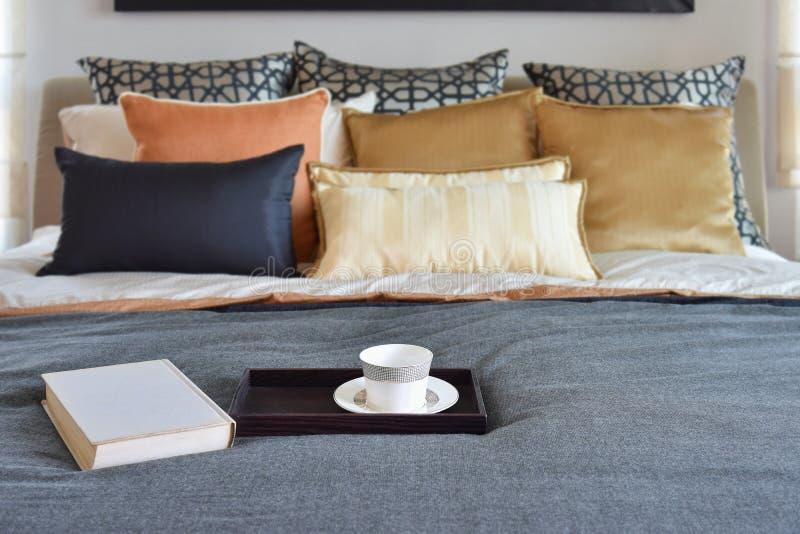 Modernt sovrum med tekoppen på det dekorativa trämagasinet arkivfoto