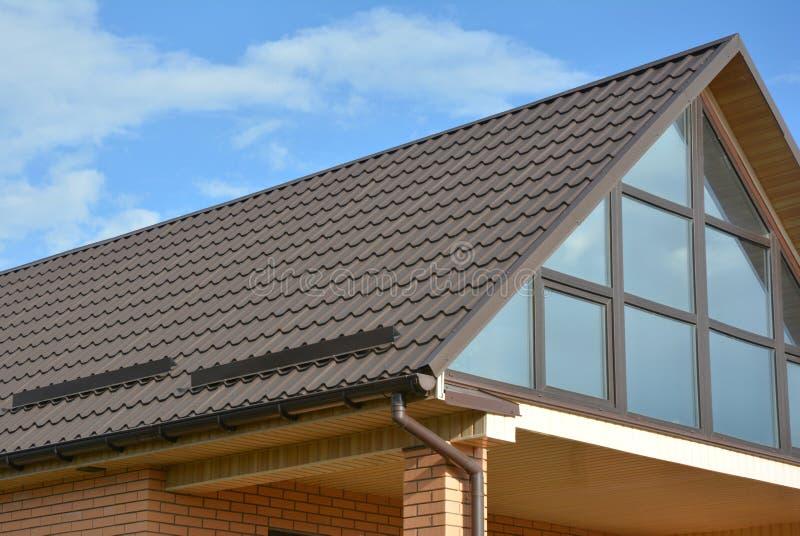 Modernt tak för tegelplatta för husloftmetall med det panorama- glasväggfönstret och takavloppsrännan royaltyfri fotografi