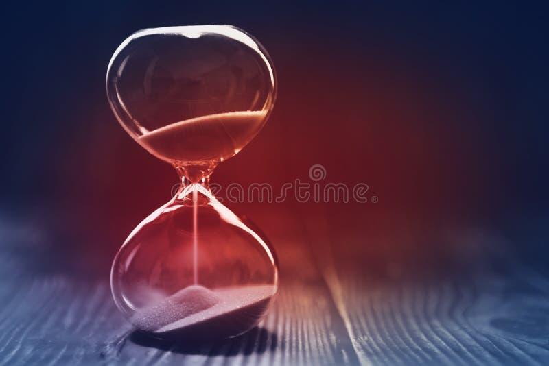 Modernt timglas med mörk bakgrund, sand som sipprar till och med kulorna av ett kristallsandexponeringsglas, med rött ljus i mitt royaltyfri foto