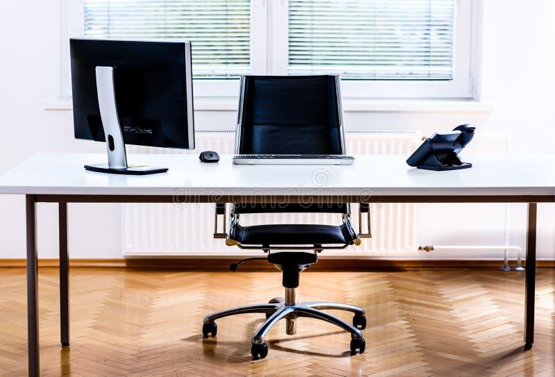 Modernt tomt skrivbord för kontorsutrymme med datoren, telefonen och stol arkivbilder
