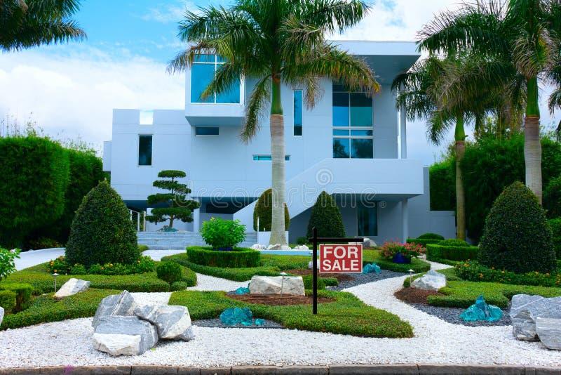 Modernt tropiskt herrgårdhus med palmträd och zenträdgård med den TILL SALU gården för tecken framtill arkivfoton