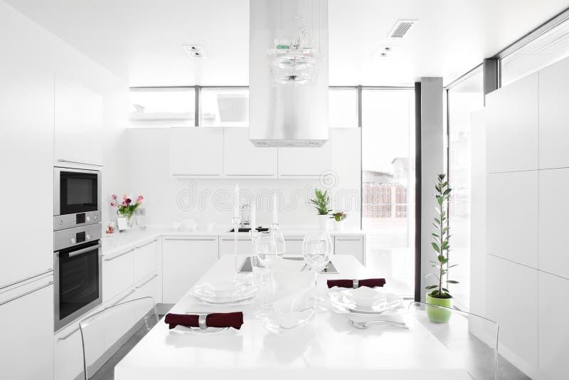 Modernt vitt kök med stilfullt möblemang royaltyfria foton