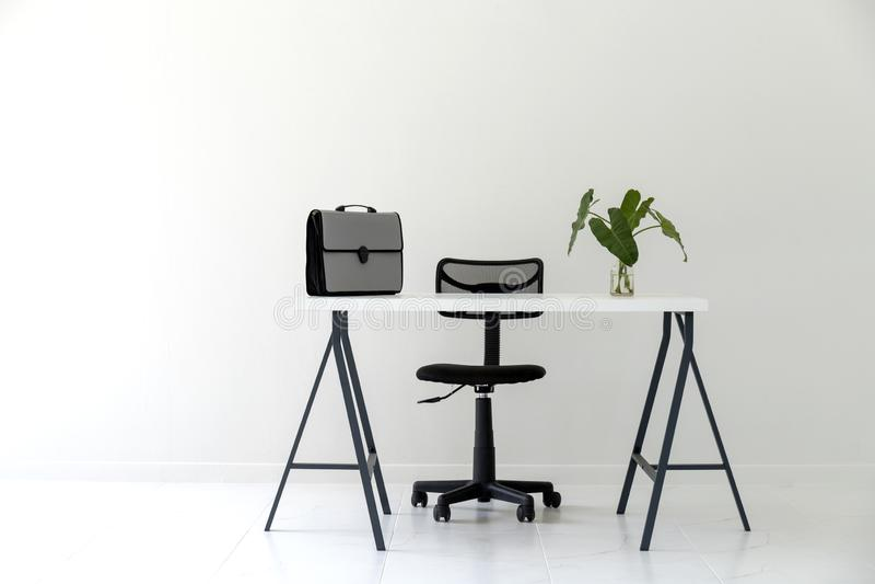 Modernt vitt kontor som är inre med den vita tabellen, svart stol, dokumentpåsen och den gröna bladvasen fotografering för bildbyråer