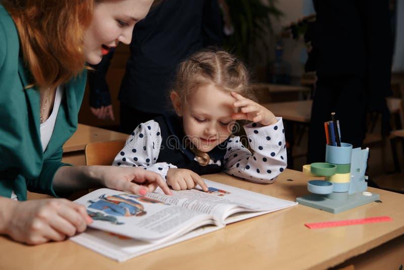Moderportionunge efter skola förskolebarnet som gör läxa med hjälp av, handleder hem- undervisningbegrepp arkivbild