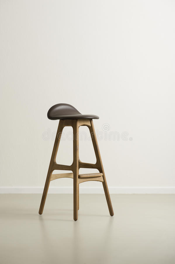 Moderrn wooden bar stool with a leather seat stock photo