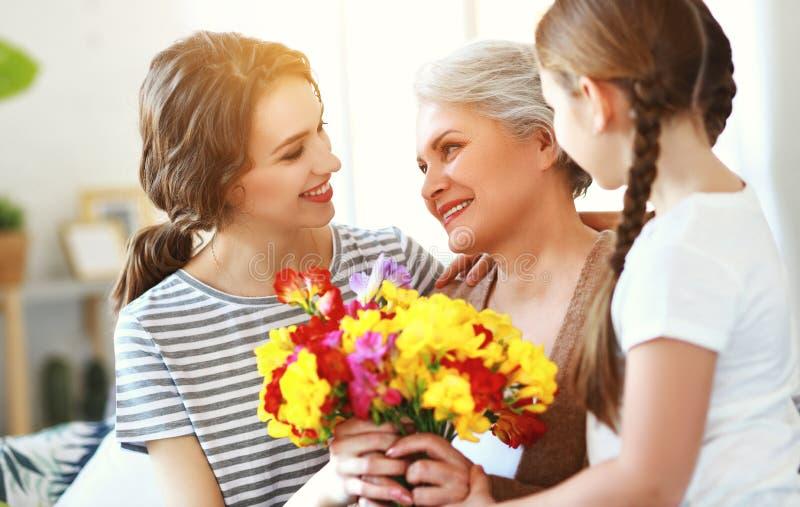 Moders dag! tre utvecklingar av familjmoder, farmor och dotter gratulerar på ferien, ger blommor royaltyfri foto