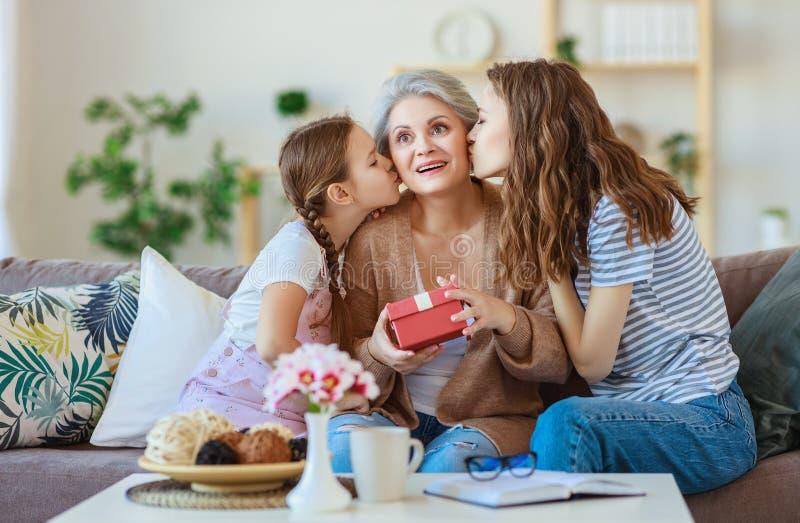 Moders dag! tre utvecklingar av familjmoder, farmor och dotter gratulerar på ferien, ger blommor arkivfoton