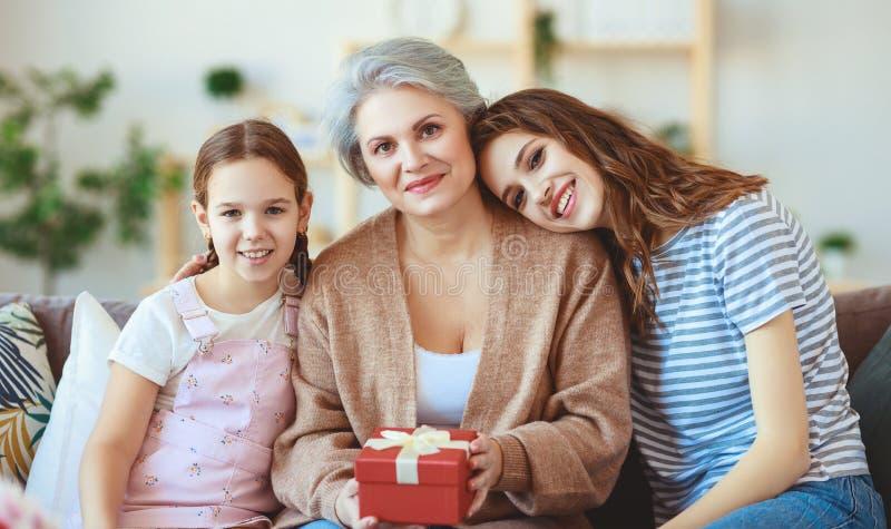 Moders dag! tre utvecklingar av familjmoder, farmor och dotter gratulerar på ferien, ger blommor arkivbild