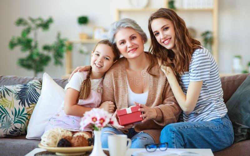 Moders dag! tre utvecklingar av familjmoder, farmor och dotter gratulerar på ferien, ger den närvarande gåvan royaltyfria foton