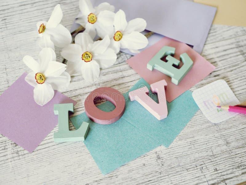 Moders ferie för dag, sammansättning av ordförälskelsen från bokstäver i stora partier, nya blommor, kuvert, papper, blyertspenno royaltyfri foto