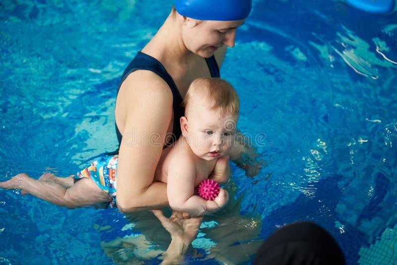Moderundervisning behandla som ett barn pojkesimning Första besöka simbassäng för barn Sunt familjlivsstilbegrepp Sikt f?r b?sta  royaltyfria bilder