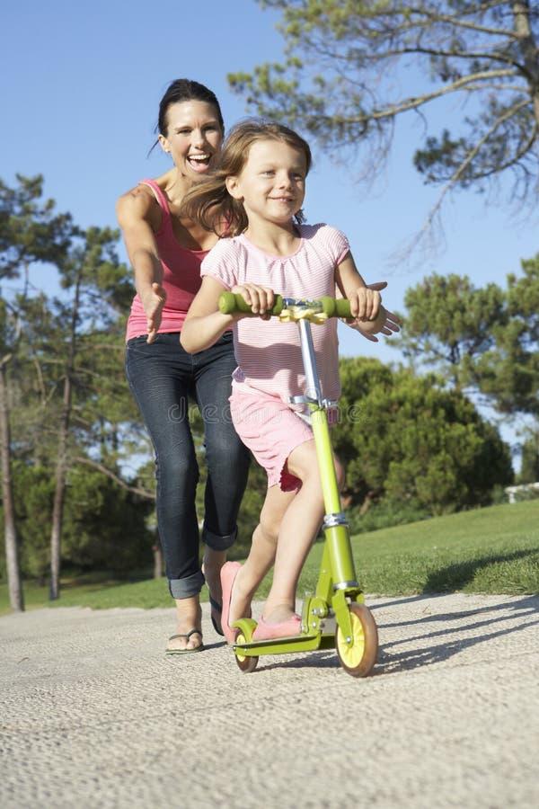 Moderundervisningdottern som rider sparkcykeln parkerar in royaltyfria bilder