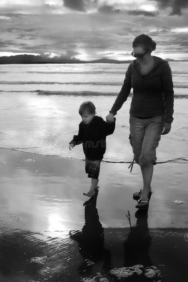 Moderungt barn på stranden som rymmer händer royaltyfria bilder