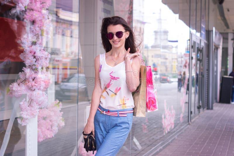 Modeschönheit geht die Stadt in den Gläsern und in den Paketen umher stockfoto
