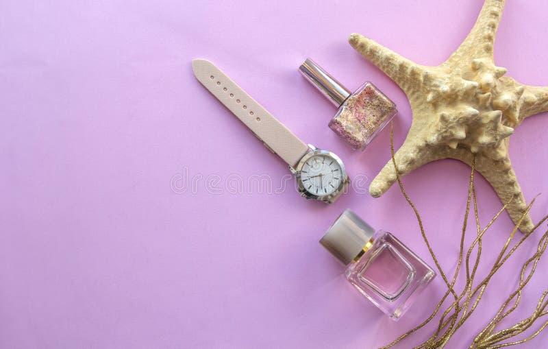 Modeschönheitszusätze - Parfüm, Nagel, Polituruhr auf rosa Hintergrund Draufsicht, flache Lage stockfoto
