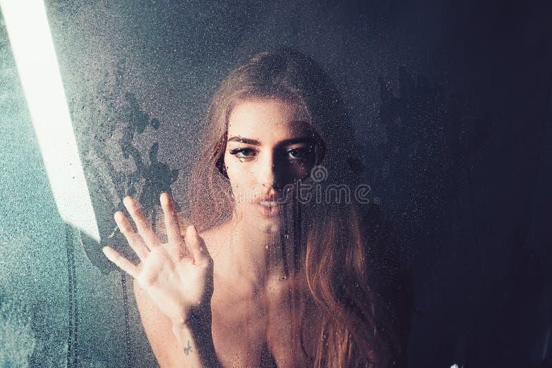 Modeskönhet och förälskelse Regn tappar på fönsterexponeringsglas i hjärtaform Den sexiga kvinnan bak det plast- arket med vatten royaltyfria bilder