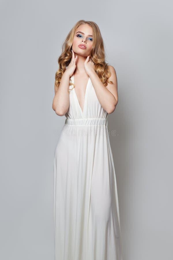 Modeskönhetstående av den härliga kvinnan i den vita klänningen som poserar på vit bakgrund arkivbild