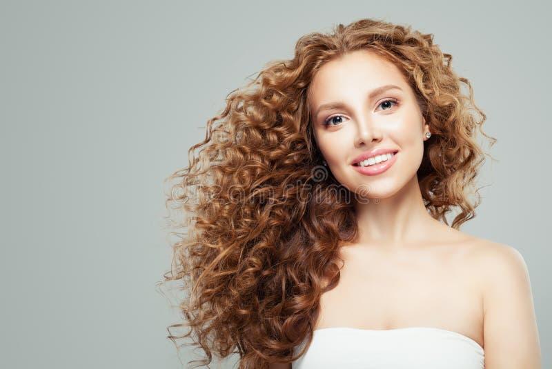 Modeskönhetstående av den unga rödhårig mankvinnan med lång sund grå bakgrund för lockigt hår royaltyfri fotografi