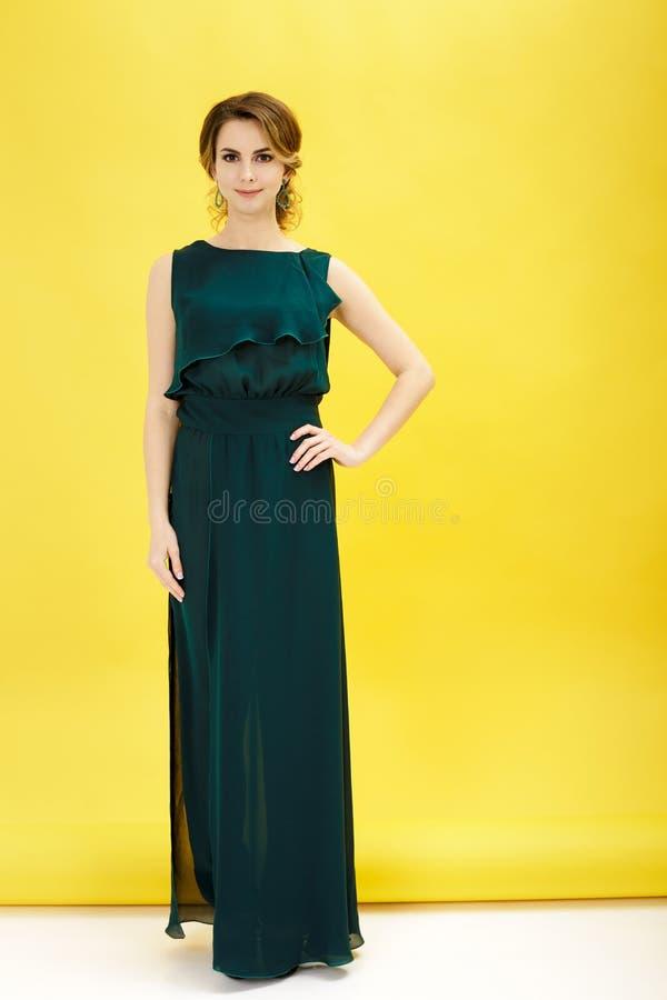 Modeskott av den härliga kvinnan i grön klänning på gul bakgrund royaltyfri foto