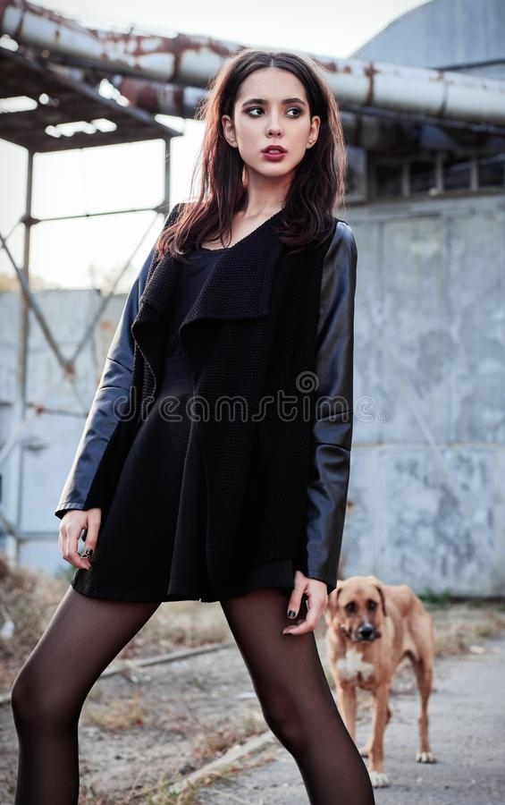 Modeskott: härligt vagga anseendet för omslaget och för hunden för informell modell för flicka det iklädda svarta på det industri royaltyfria bilder