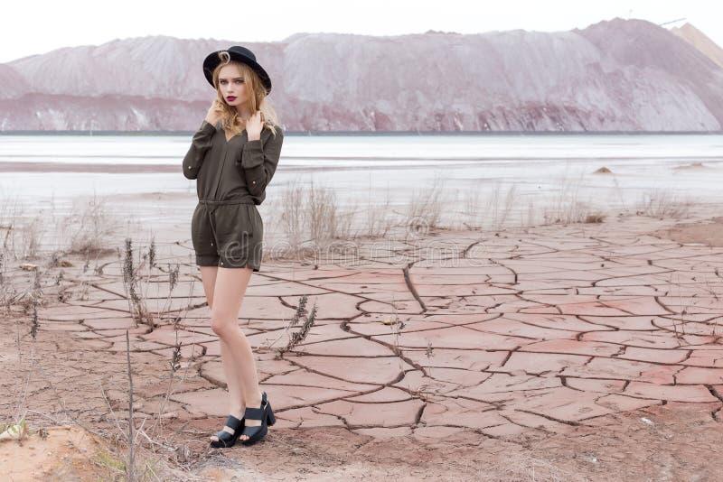 Modeskottet av en härlig sexig flicka i en svart hatt tas bort i öknen för tidskriften royaltyfria bilder