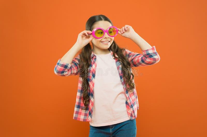 Modesonnenbrille, die Kinderaugen geschützt hält und gut schaut Kleines Mode-Modell auf orange Hintergrund adorable lizenzfreie stockfotos