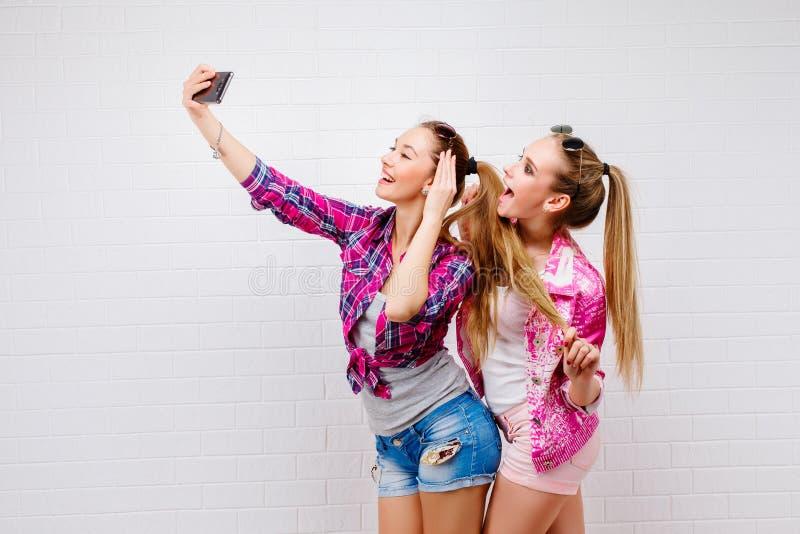 Modestående av att posera för två vänner modern livsstil Två stilfulla sexiga hipsterflickabästa vän som är klara för parti Två royaltyfria foton