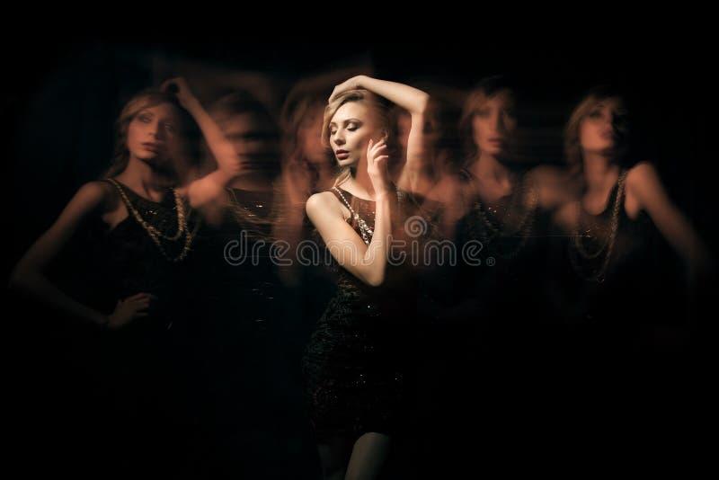 Modestående av blondiedamen i mörk klänning med sex genomskinliga klon fotografering för bildbyråer