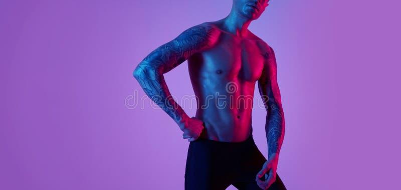Modestående av den attraktiva mannen för sportpassform Manlig naken torso tatuerade händer Pråligt studioljus för färg fotografering för bildbyråer