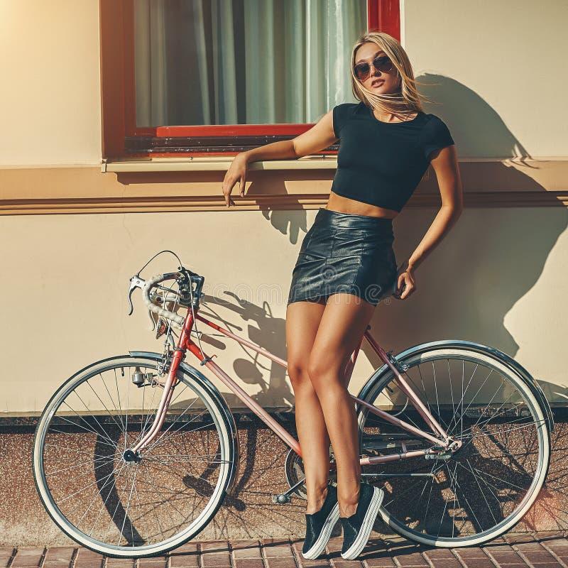 Modestående av den härliga blonda flickan nära tappningcykeln arkivbilder