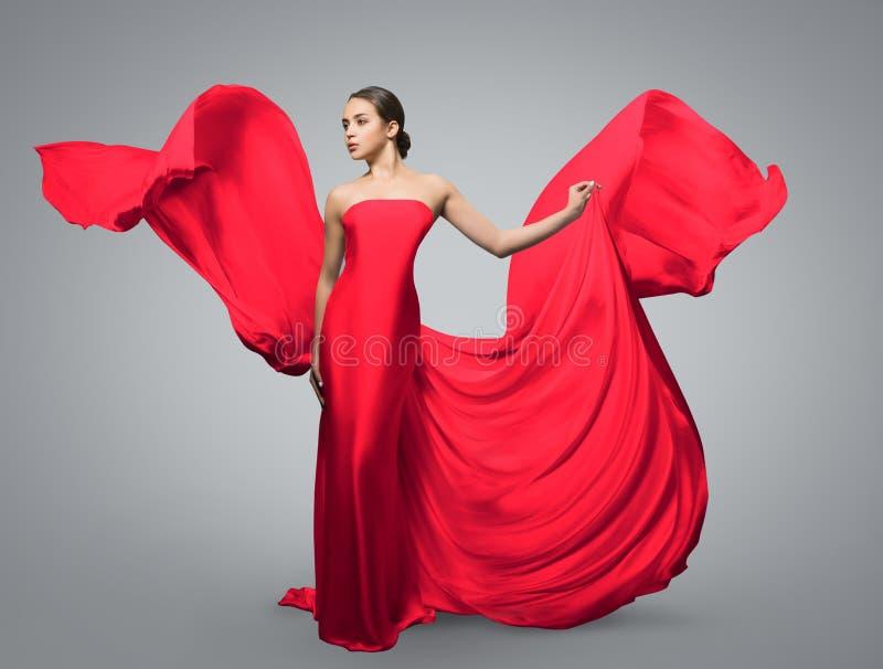 Modestående av den härliga kvinnan, i att vinka den röda klänningen Ljust tyg flyger i vinden royaltyfria bilder