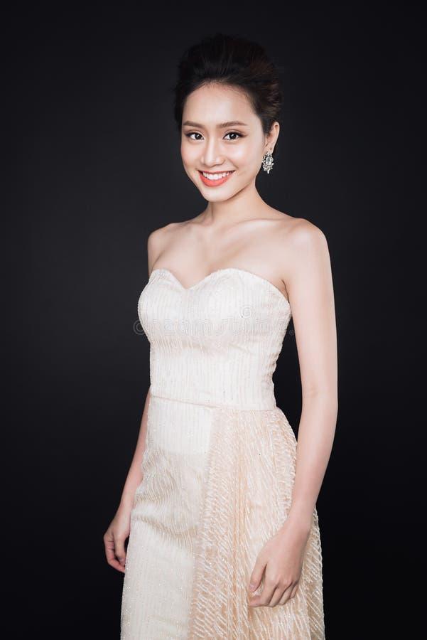 Modestående av den härliga unga asiatiska kvinnan i den vita klänningnollan royaltyfria bilder