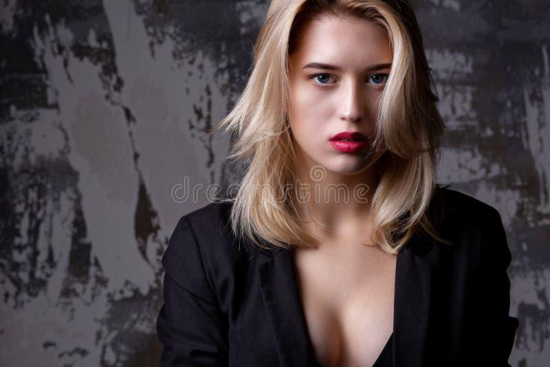Modestående av den lyxiga blonda modellen med perfekt hud som poserar på studion med skuggor Töm utrymme arkivfoton