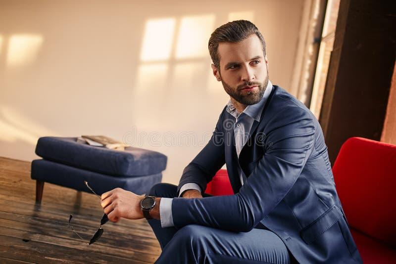 Modestående av den sexiga attraktiva affärsmannen i en stilfull dräkt royaltyfria foton