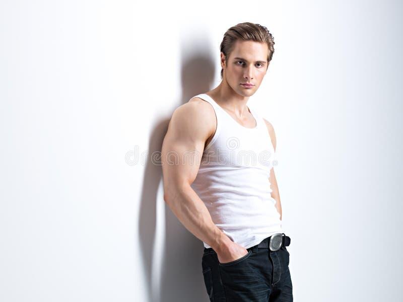 Modestående av den sexiga unga mannen. arkivbild