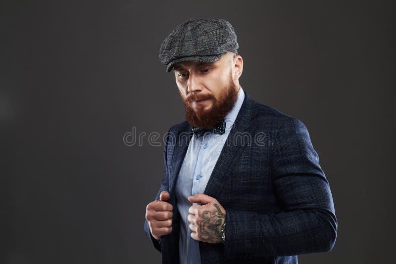 Modestående av den skäggiga mannen i dräkt Gammal Hipsterpojke Stilig man i hatt _ arkivbild