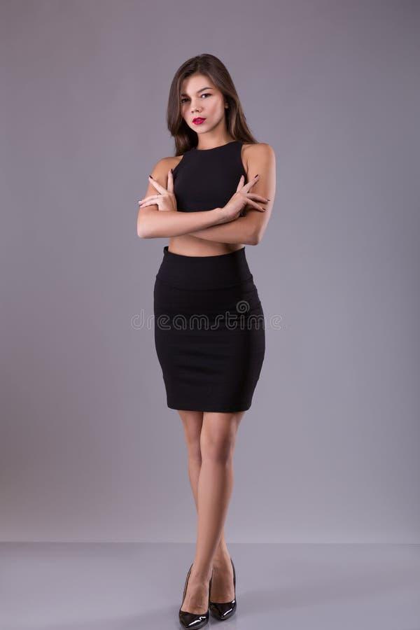 Modestående av den slanka kvinnan för härlig brunett i liten svart klänning med långt sunt hår, över grå bakgrund 15 woman young royaltyfria bilder