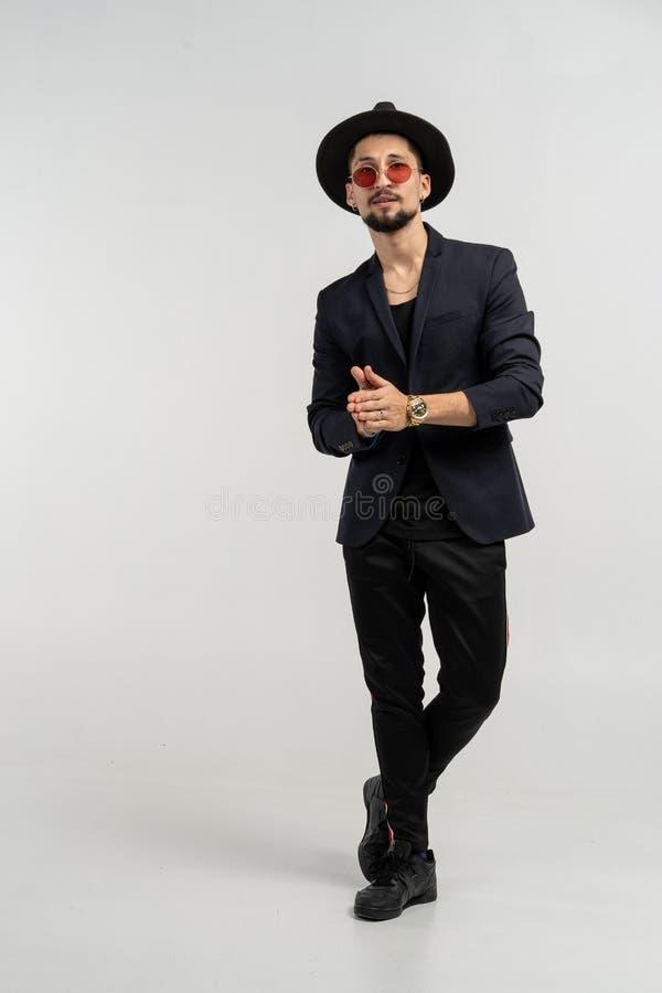 Modestående av den stiliga eleganta mannen i svart dräkt och hatten som poserar i studio arkivfoton