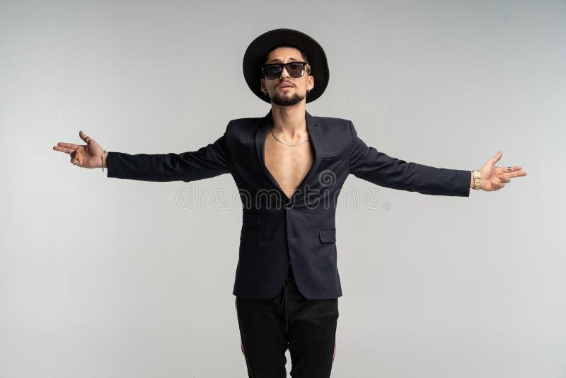 Modestående av den stiliga eleganta mannen i svart dräkt och hatten som poserar i studio fotografering för bildbyråer