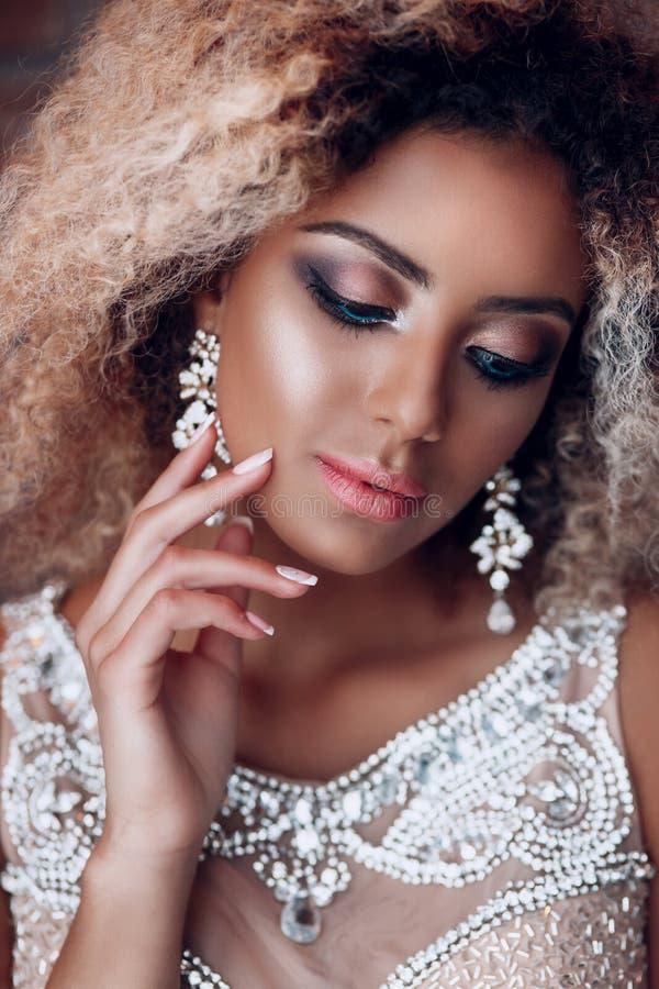 Modestående av den unga härliga afro amerikanska kvinnan med smycken och aftonsmink royaltyfri fotografi