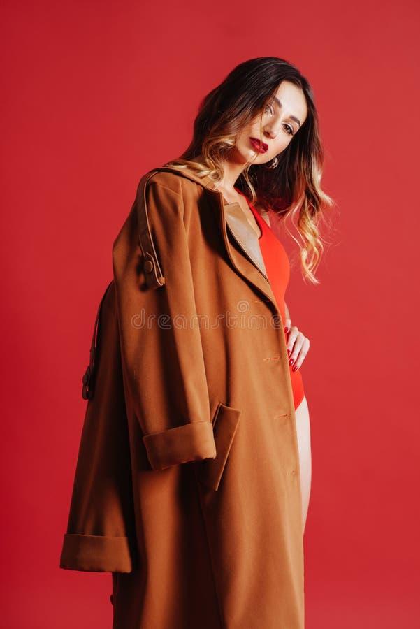 Modestående av den unga kvinnan i omslag och röd baddräkt arkivfoton