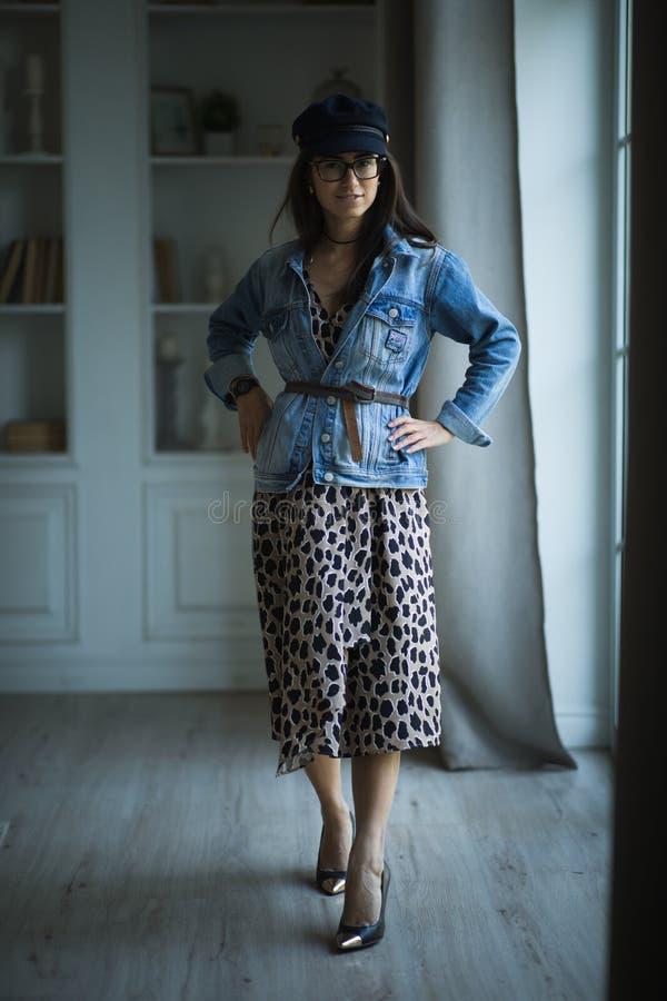 Modestående av det unga härliga kvinnliga modellanseendet i leopardklänning i inre studio royaltyfri foto