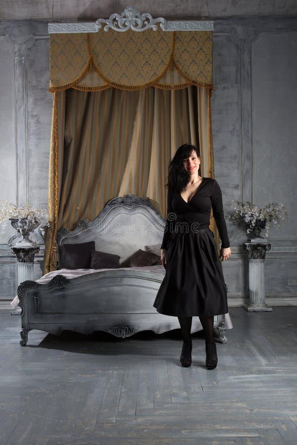 Modestående av det unga härliga kvinnliga modellanseendet i svart sexig klänning i inre studio royaltyfri bild