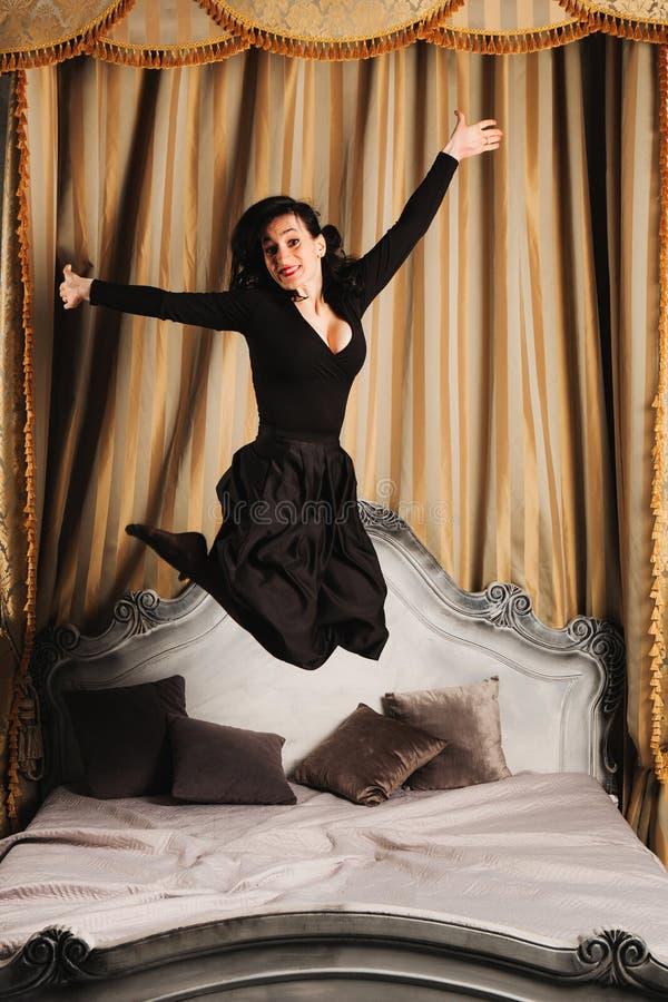 Modestående av det unga härliga kvinnliga modellanseendet på säng i svart sexig klänning i inre studio royaltyfria bilder